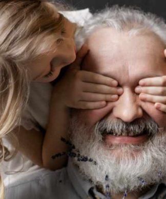 une petite fille cache les yeux de son grand père